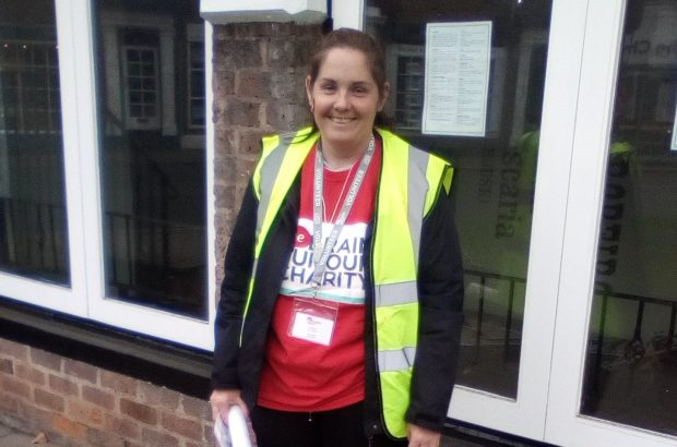 Lady in a high vis vest smiling at the camera