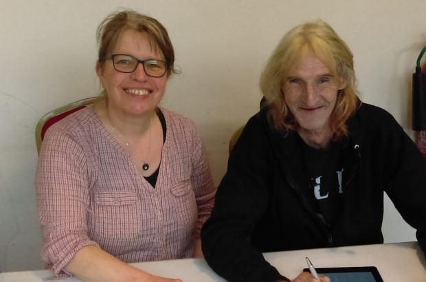 New Leaf participant, Wolfie, on a tablet. Sat with his New Leaf employment mentor, Helen
